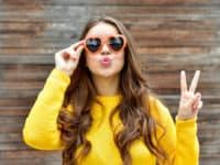 keratin braune haare sonnenbrille mit herz gelber pulli bh peace mit finger kussmund holz hintergrund klein