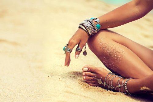 Frau im Sand braune Haut Fuß- und Fingernägel mit Schmuck
