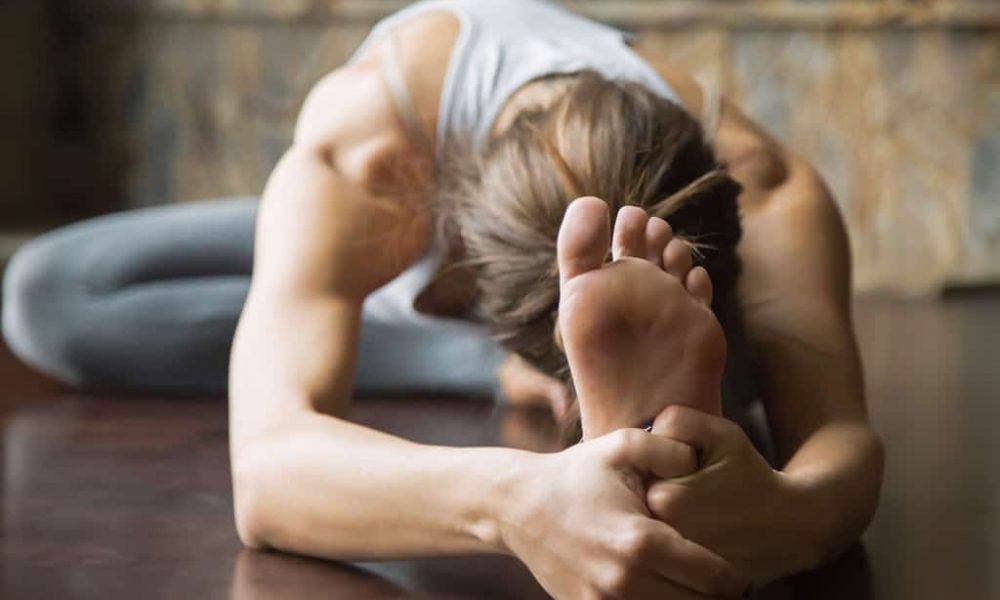 Sportliche Frau dehnt sich macht Yoga