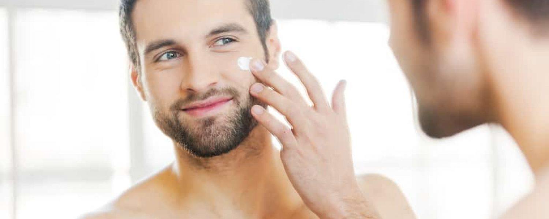 Hautpflege Gesichtscreme Mann braune haare lächeln spiegel