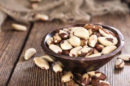 Nüsse in Holzschale auf Tisch Paranüsse Chrom katawan