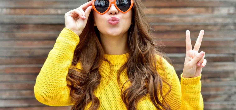 keratin braune haare sonnenbrille mit herz gelber pulli bh peace mit finger kussmund holz hintergrund